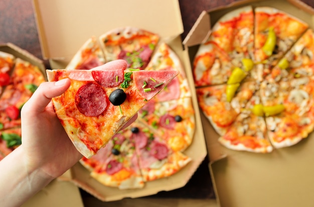 Mano femminile che prende fetta di pizza fresca dalla scatola di consegna. vista dall'alto, sfondo scuro. cibo spazzatura