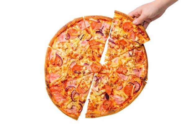 Mano femminile che prende la fetta fresca e saporita della pizza isolata su fondo bianco. pizza con peperoni, prosciutto, formaggio, carne e cipolla