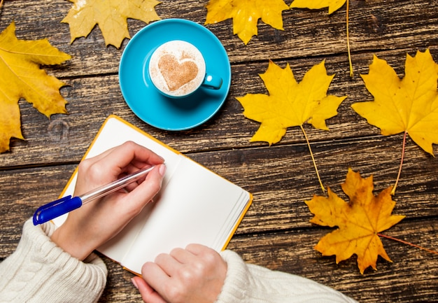 Mano femminile che scrive qualcosa in taccuino vicino alla tazza di caffè