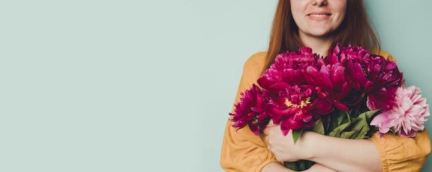 Mano femminile che tiene bellissimo bouquet con peonie profumate