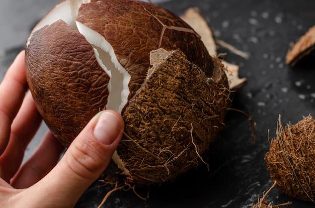 Mano femminile che tiene cocco rotto