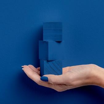 Mano femminile che tiene i cubi impilati