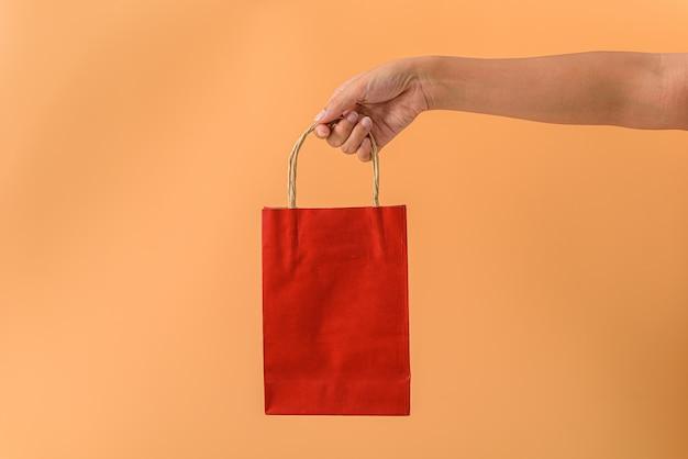 Mano femminile che tiene i sacchetti della spesa rossi del papaer