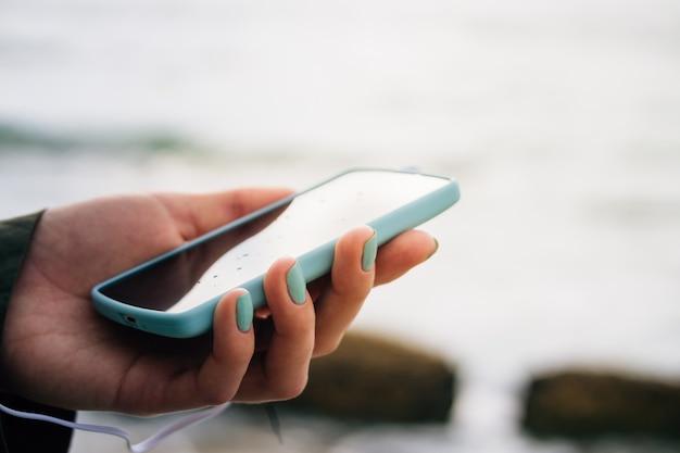 Mano femminile che tiene il telefono cellulare contro il mare