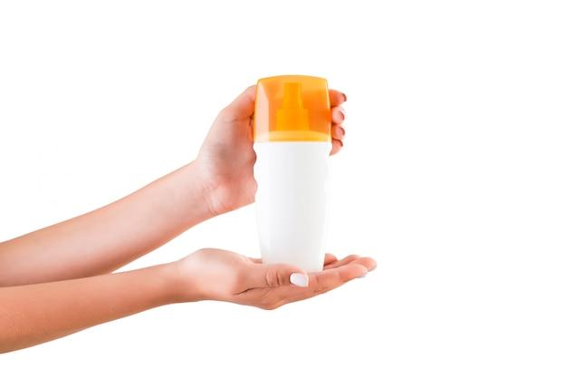 Mano femminile che tiene la bottiglia di crema di lozione isolata,