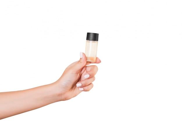 Mano femminile che tiene la bottiglia di crema di lozione