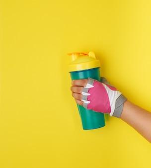 Mano femminile che tiene la bottiglia di plastica blu dell'agitatore con un tappo giallo