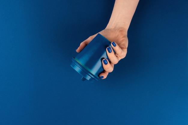 Mano femminile che tiene la tazza di caffè asportabile contro la tavola blu classica, vista superiore