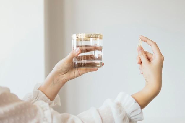 Mano femminile che tiene omega 3 capsula di integratore di olio di pesce e bicchiere d'acqua
