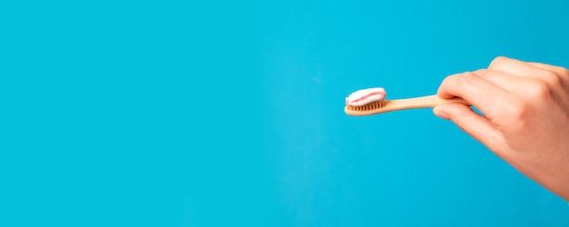 Mano femminile che tiene spazzola naturale di bambù con dentifricio in pasta su fondo blu