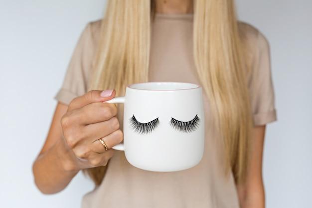 Mano femminile che tiene tazza con ciglia finte.