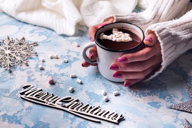 Mano femminile che tiene tazza di cacao caldo