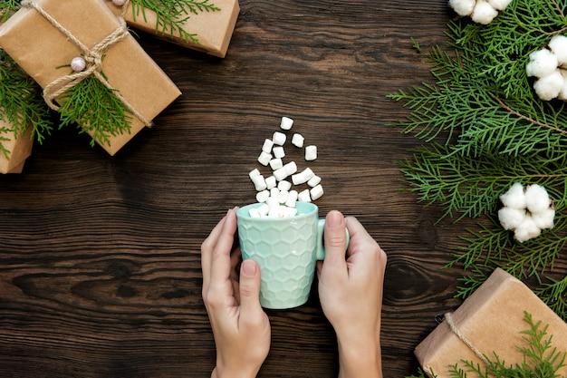 Mano femminile che tiene tazza di cioccolato con marshmallow e scatole regalo su legno scuro