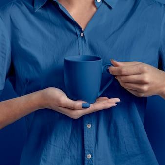 Mano femminile che tiene tazza