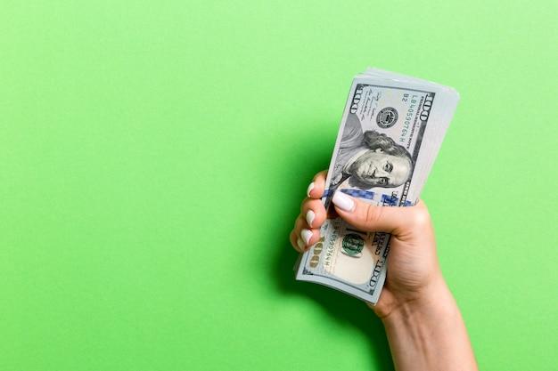 Mano femminile che tiene un centinaio di banconote in dollari