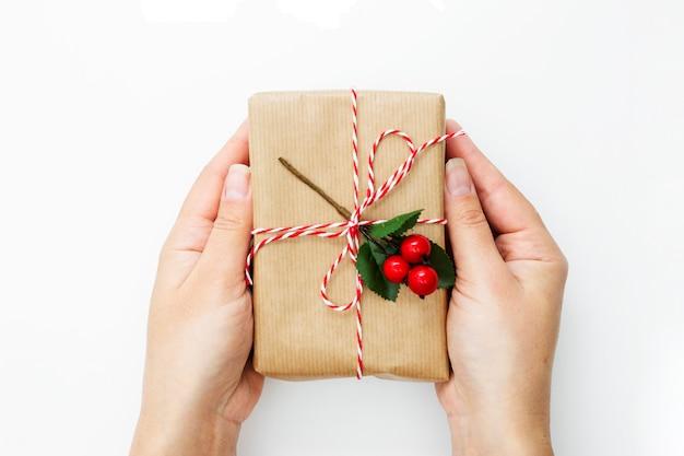Mano femminile che tiene un contenitore di regalo, avvolto in carta del mestiere isolata sopra fondo bianco.