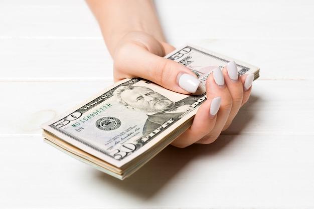 Mano femminile che tiene un pacco di soldi su di legno. vista prospettica di cinquanta e altre banconote in dollari.