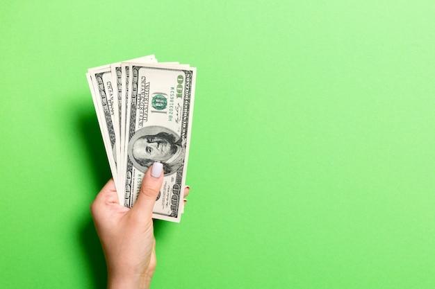 Mano femminile che tiene un pacco di soldi su fondo variopinto. vista dall'alto di banconote da cento dollari. concetto di stipendio