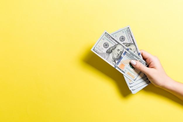 Mano femminile che tiene un pacco di soldi. vista dall'alto di banconote da cento dollari. concetto di stipendio con spazio vuoto per il vostro disegno