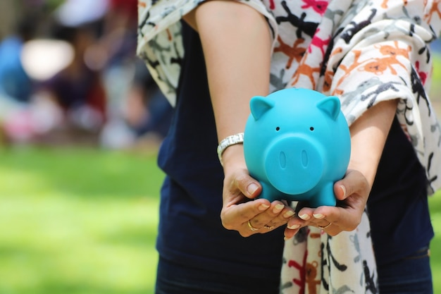 Mano femminile che tiene un porcellino salvadanaio blu, idee di investimento finanziario o attività bancarie