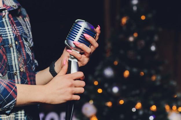 Mano femminile che tiene un singolo microfono retrò