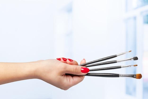 Mano femminile che tiene una spazzola professionale di trucco