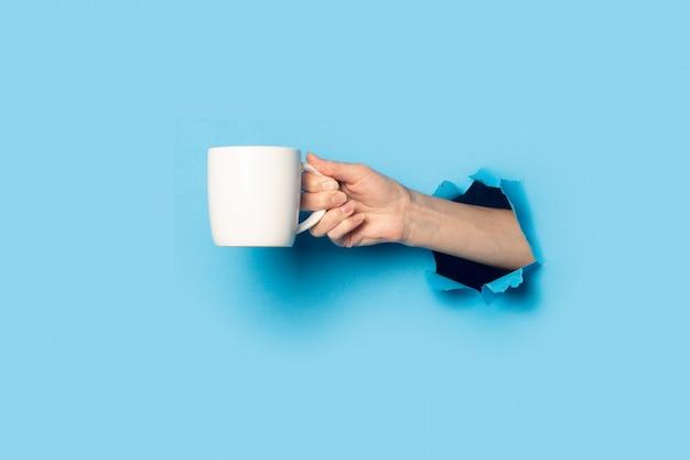 Mano femminile che tiene una tazza bianca su sfondo blu brillante