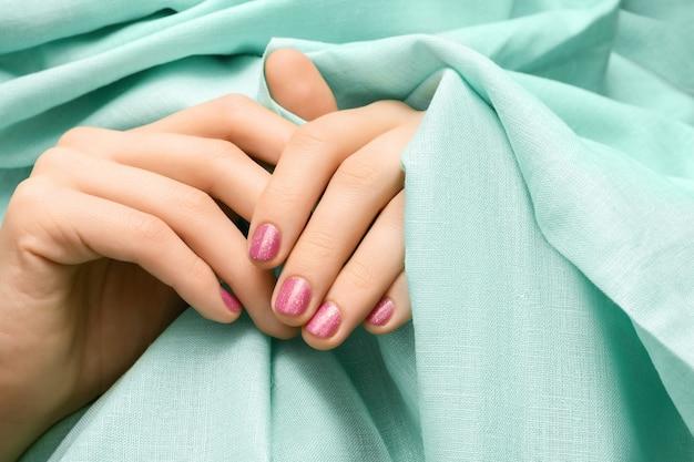 Mano femminile con design a unghie con glitter rosa.