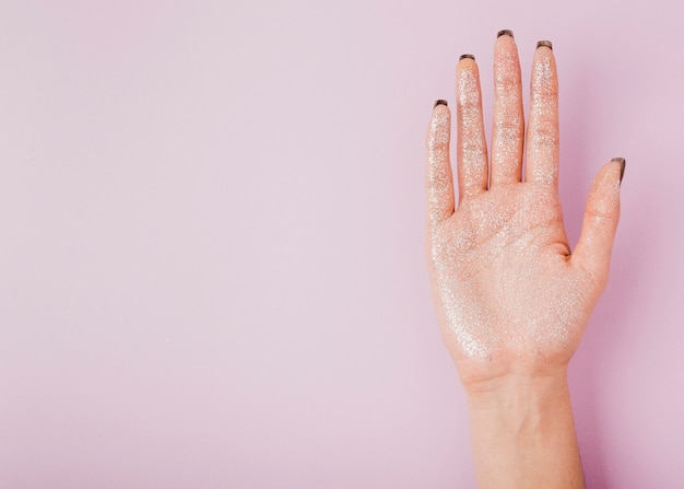 Mano femminile con glitter e copia spazio sfondo rosa