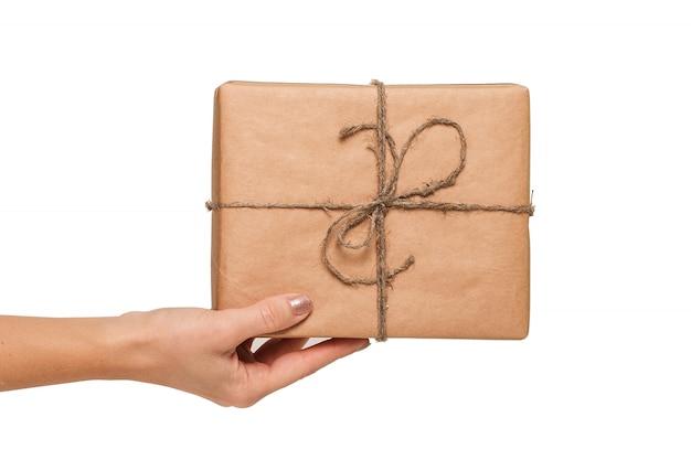 Mano femminile con il contenitore di regalo isolato su bianco