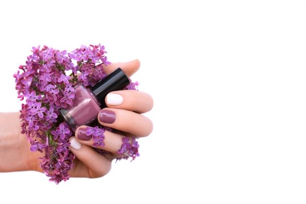 Mano femminile con il disegno bianco e viola dell'unghia che tiene i fiori lilla