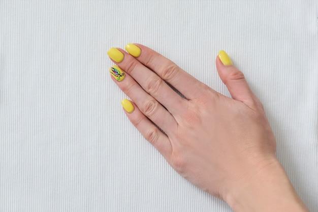 Mano femminile con il manicure giallo su tessuto bianco.