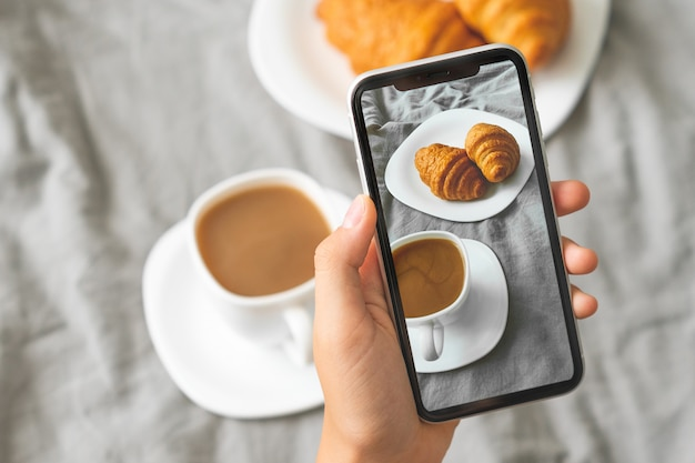 Mano femminile con il telefono cellulare che prende immagine del caffè e dei croissant saporiti della prima colazione