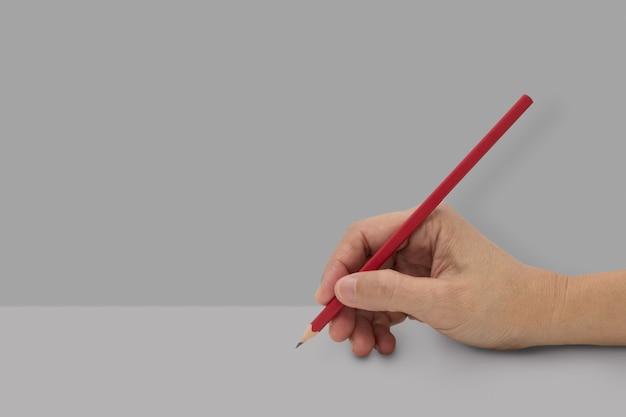 Mano femminile con la matita di colore rosso