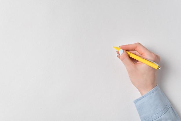 Mano femminile con la penna su fondo bianco. copia spazio