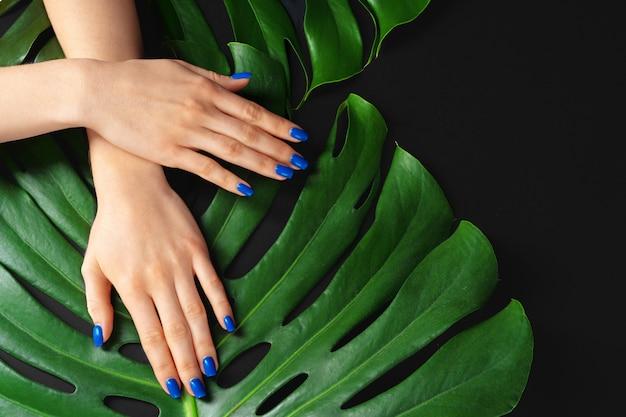 Mano femminile con le unghie di colore blu classico manicure su foglia di monstera. foto creativa
