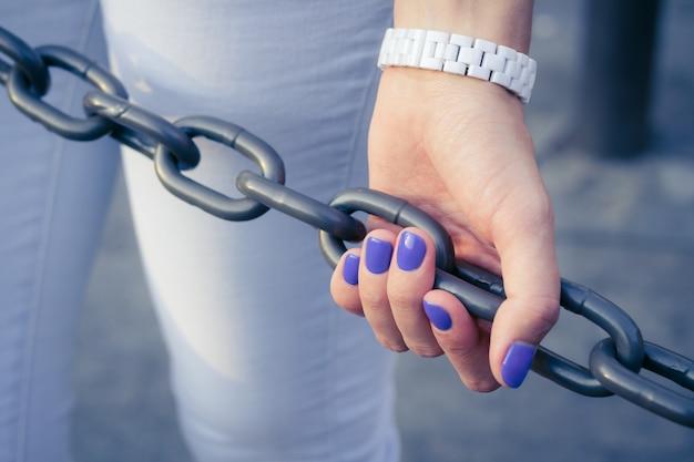 Mano femminile con manicure blu che tiene una catena di metallo