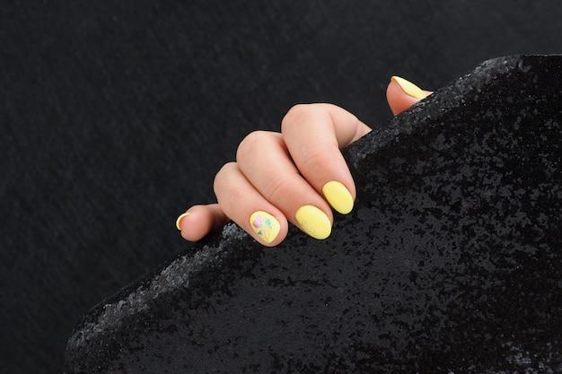 Mano femminile con manicure giallo brillante tiene un panno nero lucido su sfondo nero. copia spazio.