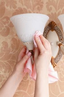 Mano femminile con panno in microfibra asciutto pulizia di un lampadario in camera