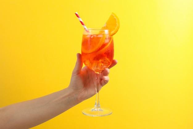 Mano femminile con un bicchiere di aperol spritz cocktail su giallo