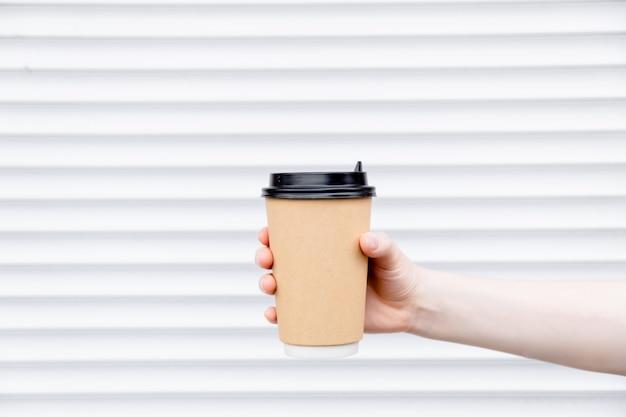 Mano femminile della donna con il latte di carta della tazza di caffè. tazza in un supporto, tazza di caffè da asporto.