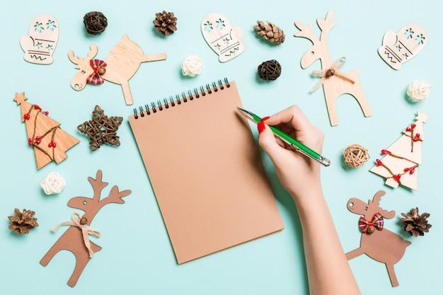 Mano femminile di vista superiore che fa alcune note nel noteebok sul blu. decorazioni e giocattoli. periodo natalizio