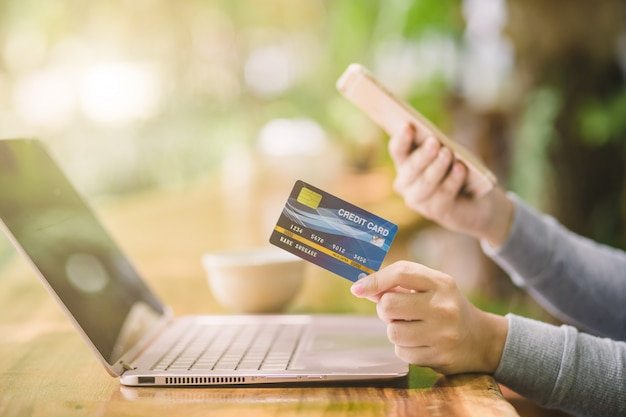 Mano femminile di yong che tiene la carta di credito di plastica e che per mezzo del computer portatile. shopping online o concetto di pagamento.