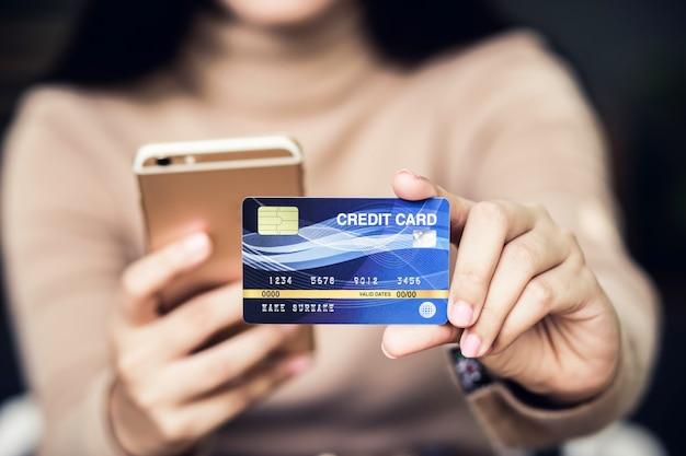Mano femminile di yong che tiene la carta di credito di plastica e per mezzo del computer portatile. shopping online o concetto di pagamento.