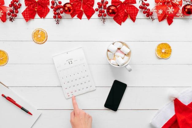 Mano femminile. donna che lavora a un tavolo da ufficio con decorazioni festive di natale