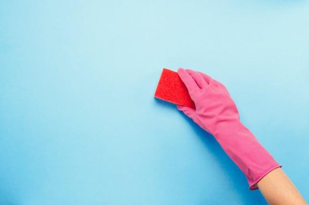 Mano femminile in guanti rosa che tengono spugna per la pulizia su un fondo blu. concetto di servizio di pulizia. vista piana, vista dall'alto