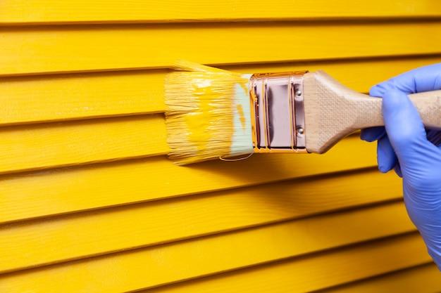 Mano femminile in guanto di gomma con la spazzola che dipinge porta di legno con pittura gialla