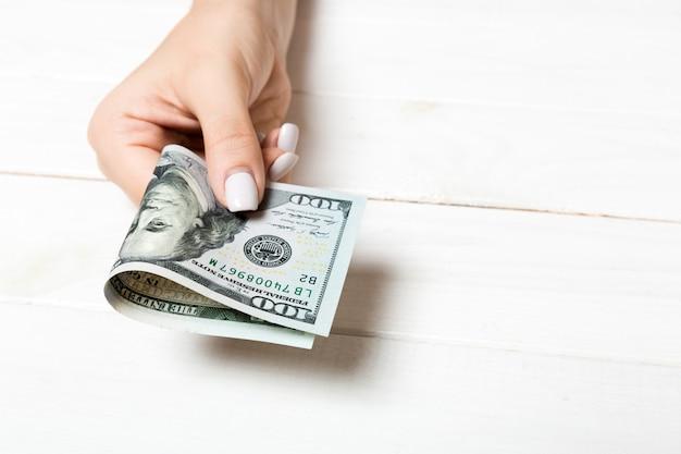 Mano femminile in possesso di un pacco di banconote da cento dollari