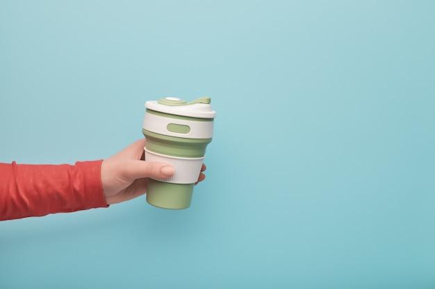 Mano femminile in possesso di una tazza riutilizzabile in silicone.