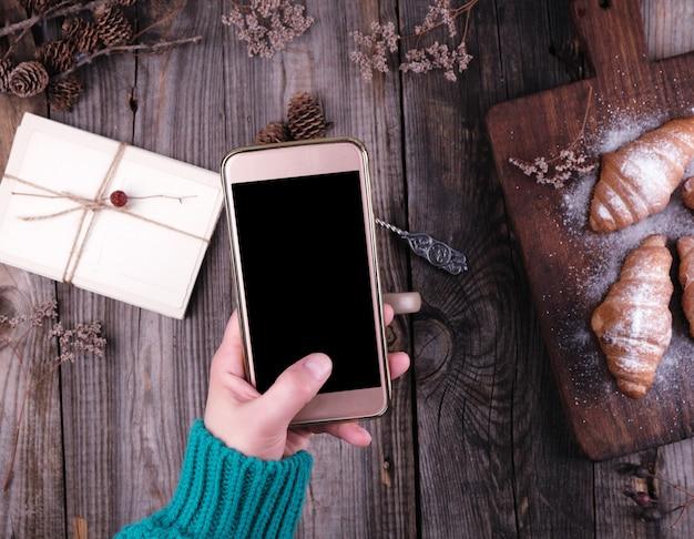 Mano femminile in un maglione lavorato a maglia verde che tiene uno smartphone con uno schermo nero in bianco